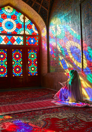 SHIRAZ, IRAN - March 01, 2016: Young Muslim woman praying in Nasir Al-Mulk Mosque (Pink Mosque), Iran, Shiraz Editorial