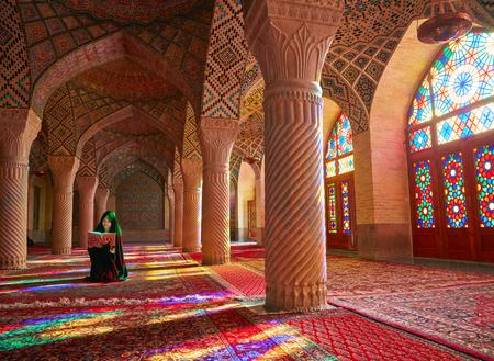 pray: SHIRAZ, IRAN - March 01, 2016: Young Muslim woman praying in Nasir Al-Mulk Mosque (Pink Mosque), Iran, Shiraz Editorial