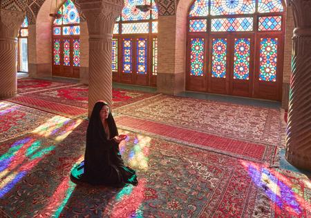 Shiraz, IRAN - 1 maart 2016: Jonge Moslimvrouw bidden in Nasir Al-Mulk Mosque (Roze Moskee), Iran, Shiraz