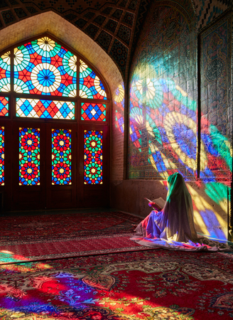 Young Muslim woman praying in Nasir Al-Mulk Mosque (Pink Mosque). Iran, Shiraz