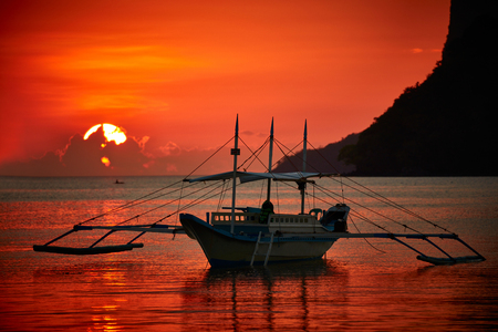 nido: Traditional filippino boat at El Nido bay in sunset lights.  Palawan island, Philippines Stock Photo