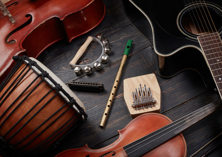 harmonica: Set of musical instruments on dark wooden background: guitar, violin, harmonica, cello and others. Top view Stock Photo