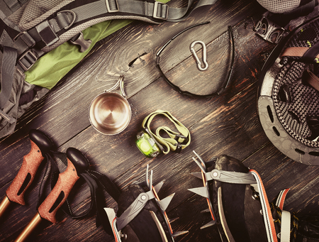 Climber accessories set on dark wooden background: boots with crampon, backpack, sunglasses, flashlight and others. Top view Stock fotó