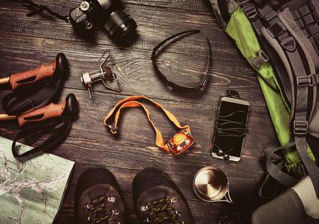 Senderismo accesorios fijados en fondo oscuro de madera: botas, mochila, gafas de sol, cámara de fotos, un mapa, un teléfono inteligente, una linterna y otros. Vista superior. efecto retro de la vendimia Foto de archivo