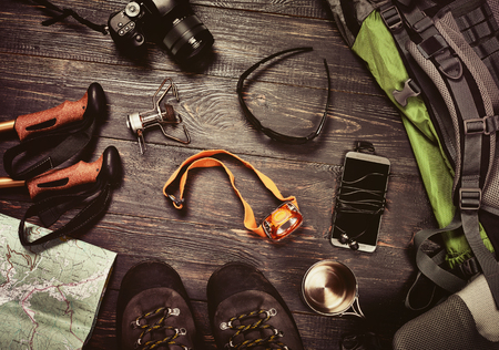 Hiking accessories set on dark wooden background:  boots, backpack, sunglasses, photo camera, map, smartphone, flashlight and others. Top view. Vintage retro effect Standard-Bild