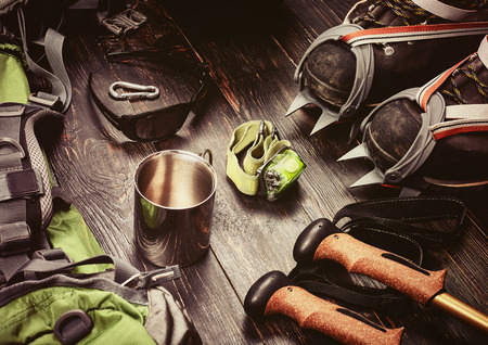 crampon: Climber accessories set on dark wooden background:  boots with crampon, backpack, sunglasses, flashlight and others. Top view