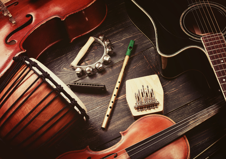 cellos: Set of musical instruments on dark wooden background: guitar, violin, harmonica, cello and others. Top view. Vintage retro effect filtered, hipster style Stock Photo