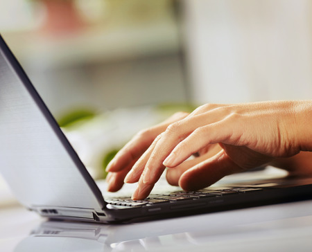 Woman hands typing on laptop Stock Photo