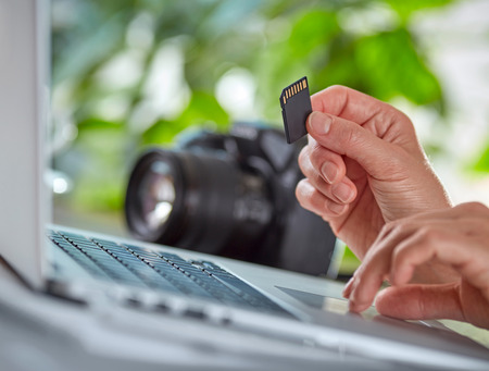 Woman copying photos from camera to her laptop.  Hand with SD card. Shallow DOF