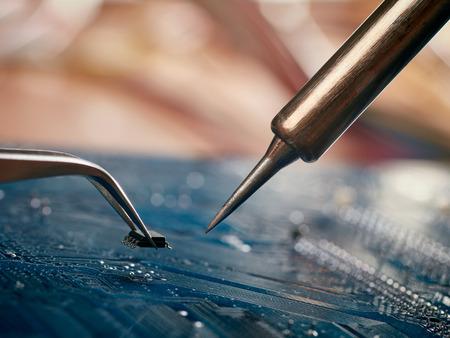 Computer repair concept. Tweezers with chip and soldering Iron Standard-Bild