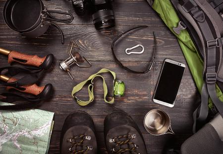 Accessori da trekking. Stivali, zaino, occhiali da sole, macchina fotografica, mappa, smartphone, torcia elettrica e altri. Vista dall'alto.