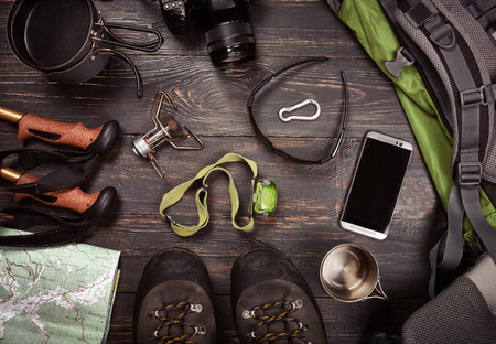 Hiking accessories. Boots, backpack, sunglasses, photo camera, map, smartphone, flashlight and others. Top view. Standard-Bild