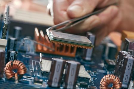 microprocessor: Engineer plug in CPU microprocessor to motherboard socket Stock Photo