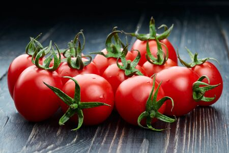 Ripe tomatoes on dark wooden background