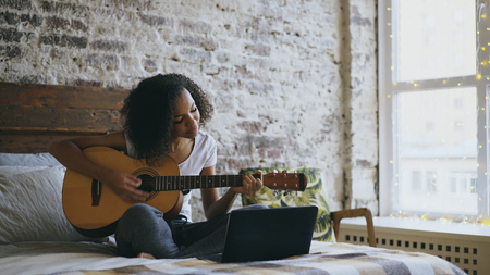 Curly african american teenager girl concentraing learning to play guitar using laptop computer sitting on bed at home