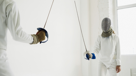 Two fencers having training attack exercises in fencing in studio Stock Photo