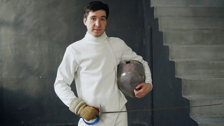 Portrait of young fencer man smiling and looking into camera indoors