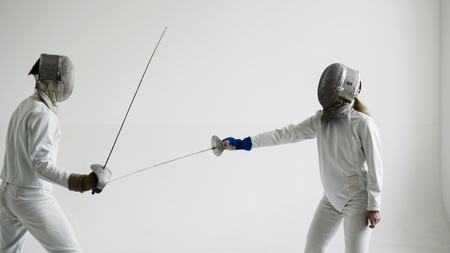 2つのフェンサーは、白い背景にフェンシングトレーニングを持っています 写真素材