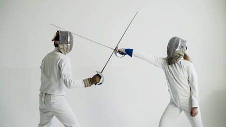 Young woman fencer having fencing training with trainer in white studio indoors Foto de archivo