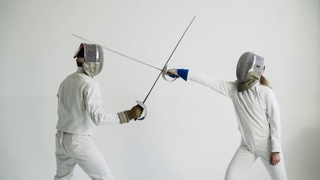 Młoda kobieta szermierz ma szermierczego szkolenie z trenerem w białym studiu indoors