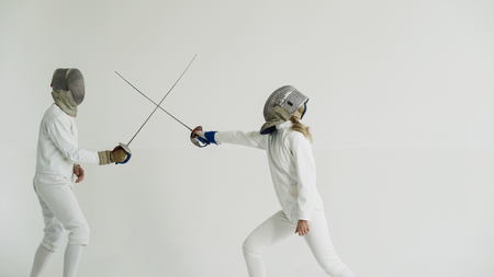 Young woman fencer having fencing training with trainer in white studio indoors Stock Photo