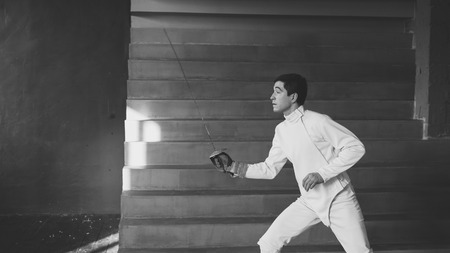 Young concentrated fencer man practice fencing exercises and training
