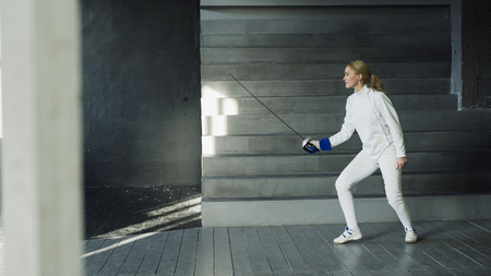 Young concentrated fencer woman practice fencing exercises and training Stok Fotoğraf