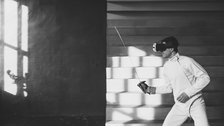 Concentrated fencer man practice fencing exercises using VR headset and training simulator competition game indoors Stock Photo