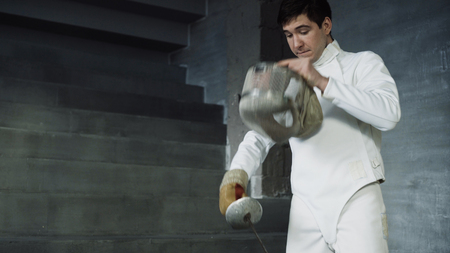 Fencer man putting on protective clothes and helmet prepare for fencing competition indoors