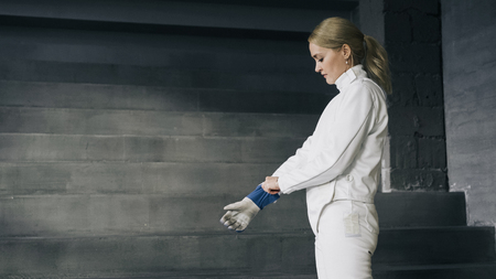 Fencer woman putting on protective clothes and helmet prepare for fencing competition indoors