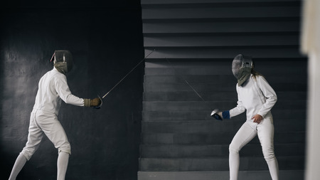 Two fencers man and woman have fencing match indoors Stock Photo