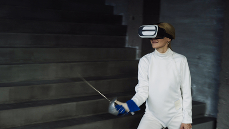 Concentrated fencer woman practice fencing exercises using VR headset and training simulator competition game indoors