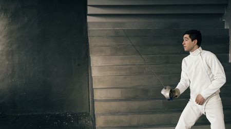 Young concentrated fencer man practice fencing exercises and training for competition in studio indoors Stok Fotoğraf