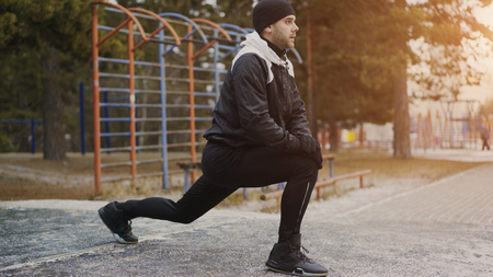 Attractive man runner doing stretching exercise preparing for morning workout and jogging in winter park Stock Photo