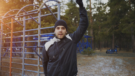 Young athlete man warming up before workout training in winter park Stok Fotoğraf