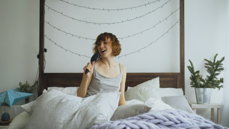 Attractive cheerful woman dancing and singing with comb like microphone sitting in bed at home