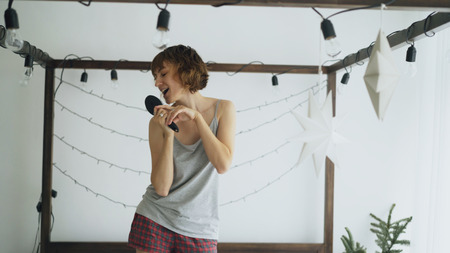 Attractive cheerful woman dancing on bed and singing with comb like microphone at home