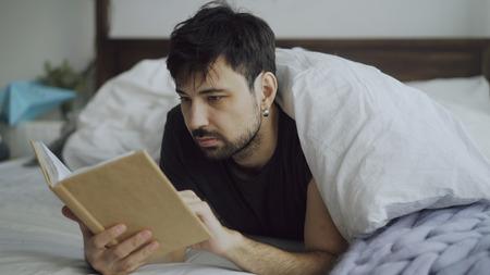 집에서 담요 아래에 침대에 누워 책을 읽고 잘 생긴 젊은 남자 스톡 콘텐츠