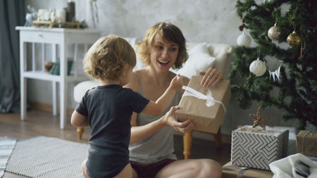 Happy mother and her little daughter unpack gift box near the Christmas tree at home Stock Photo