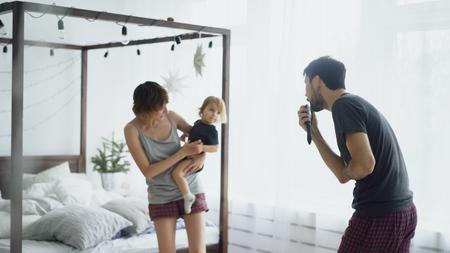 집에서 famater 노래하는 동안 침실에서 침대 근처에서 춤을 추는 행복한 가족과 작은 귀여운 딸