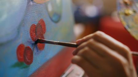 アートスタジオのキャンバスにブラシ絵画静物画で手を動かしたアーティスト女性のクローズアップ 写真素材