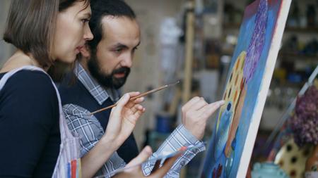 숙련 된 예술가 선생님이 예술 수업에서 학생들에게 그림의 기초를 보여주고 토론 함. 스톡 콘텐츠