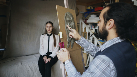 Skilled sculptor works with plasticine on canvas to create womans face of posing model in art studio