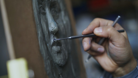 Close-up of Sculptor creating sculpture of humans face on canvas in art studio Stock Photo