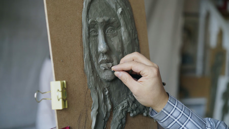 Close-up of Sculptor creating sculpture of humans face on canvas while young woman posing to him in art studio Stock Photo