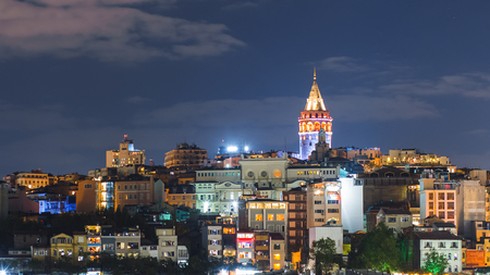 Istanbul cityscape with Galata Tower and floating tourist boats in Bosphorus night