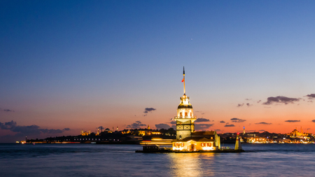 Maiden Tower or Kiz Kulesi with floating tourist boats on Bosphorus in Istanbul at night