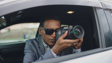 Paparazzi man sitting inside car and photographing with dslr camera Stock Photo