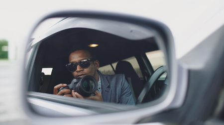 Reflection in side mirror of Paparazzi man sitting inside car and photographing with dslr camera