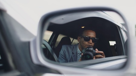 Reflection in side mirror of police man sitting inside car and photographing with dslr camera